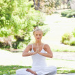 Woman in a yoga position sitting on the lawn - Stok fotoğraf
