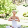 Woman in a yoga position sitting on the lawn - Lizenzfreies Foto
