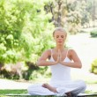 Woman in a yoga position sitting in the park - Lizenzfreies Foto