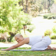 Stock Photo: Side view of womdoing stretches on lawn