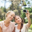 Woman taking a picture of herself and a friend - Stock Photo