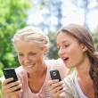 Friends in the park with their cellphones — Stock Photo