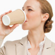 Businesswoman in a suit drinking a takeaway coffee — Stockfoto