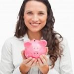 Brunette holding a piggy bank — Stock Photo #10331744