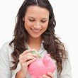 Brunette putting money in a piggy bank — Stock Photo