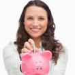 Portrait of a brunette putting money in the piggy bank — Stock Photo