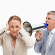 Businessman yelling with a megaphone after his colleague — Stock Photo