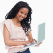 A young woman holding a laptop is smiling at the camera — Stock Photo #10332173