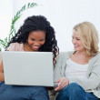 Two women with a laptop in front of them are laughing — Stock Photo #10332179