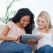 Two women sitting on a couch looking at a tablet computer — Stock Photo