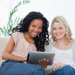 Two women smiling at the camera with a tablet computer in front — Stock Photo