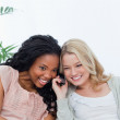 Two women are listening to a mobile phone — Stock Photo