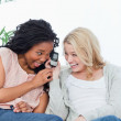 A laughing woman is holding a mobile phone up to her friends ear — Stock Photo