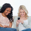 A woman holding a mobile phone is sitting on a couch with her fr — Stock Photo
