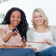 Stock Photo: Two women with popcorn and television remote control