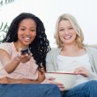 Two women with popcorn and a television remote control — Stock Photo