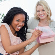 A woman holding a pink box smiles at the camera with her friend — Stock Photo