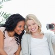 Two women are sitting down taking photo of themselves with a cam — Stock Photo #10332265