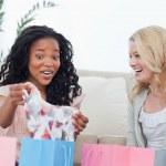 dos mujeres riendo miran ropa que compraron — Foto de Stock