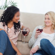 Two women sitting up against a couch are drinking wine — Stock Photo