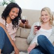 Two women smiling at the camera holding wine glasses — Stock Photo