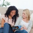 A surprised woman is reading a magazine with her friend — Stock Photo