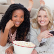 Two women lying on the ground with popcorn are smiling at the ca - Stock Photo