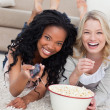Two women lying on the ground with popcorn are smiling at the ca — Stock Photo