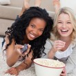 Two women lying on the ground with popcorn are smiling at the ca — Stock Photo #10332411