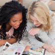 Two women lying on the floor are reading a magazine — Stock Photo #10332489