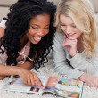 A woman is pointing at a magazine with her friend beside her — Stock Photo