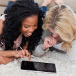 Two women are lying on the floor using a tablet — Stock Photo #10332535