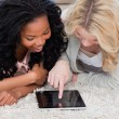 Stock Photo: Two women lying on carpet are looking at a tablet