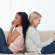 Two women sitting back to back on a couch — Stock Photo #10332639