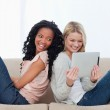 Two women sitting back to back on a couch looking at a tablet co — Stock Photo #10332648