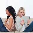 Two laughing women sitting back to back have a tablet computer — Stock Photo #10332656
