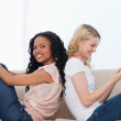 Two happy women are sitting on a couch back to back — Stock Photo #10332662