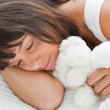 Beautiful young woman sleeping with a teddy bear — Stock Photo