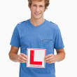 Young blond man holding a learner driver sign — Stock Photo