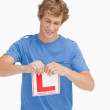 Young man ripping a learner driver sign — Stock Photo