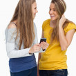 Two females student laughing while holding a cellphone — Stock Photo
