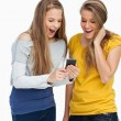 Two surprised students looking cellphone screen — Stock Photo #10335102