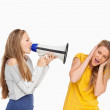 Blonde student yelling with a loudspeaker on a other girl — Stock Photo