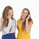 iki genç kadın telefonla gülüyor — Stok fotoğraf