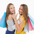 Rear view of two young women the thumb-up with shopping bags - Foto Stock