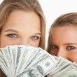Close-up of two young woman behind dollars — Stock Photo