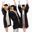 Three students in graduate robe raising their arms — Stock Photo