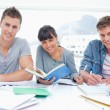 Students doing work together as they all look into the camera — Stock Photo