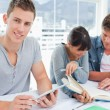 Foto de Stock  : Three smiling students sitting and doing work as one looks at th