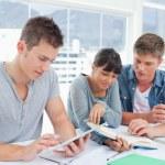 Skupina studentů sedět dohromady pomocí tablet a knihu do st — Stock fotografie